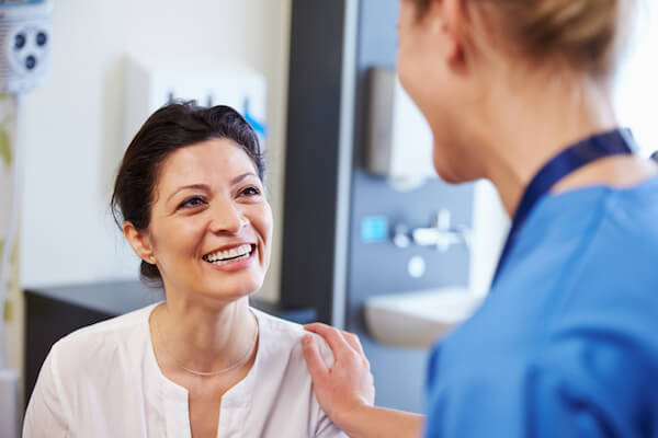 Woman smiles at her doctor in doctors office