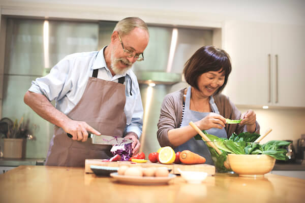 Couple chops vegetables in their kitchen