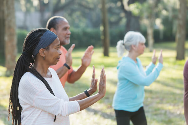 Group of adults doing tai chi outdoors