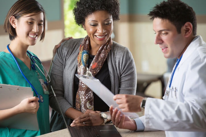 A woman reviews results with her doctor and nurse