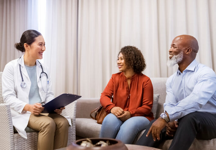 A doctor reviews information a couple