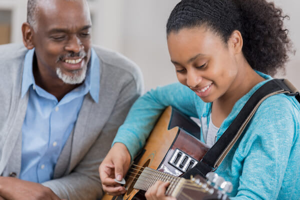A girl plays the guitar as her grandfather listens