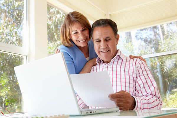 A couple smiles and reviews cost information with their laptop computer