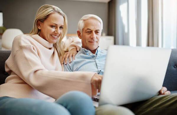 Smiling couple reviewing cost information on a laptop computer