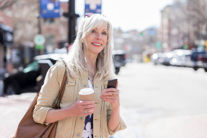 Woman waits on a ride holding her phone and coffee