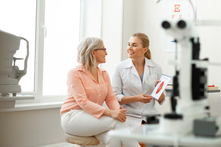 Eye doctor meets with her patient in her office