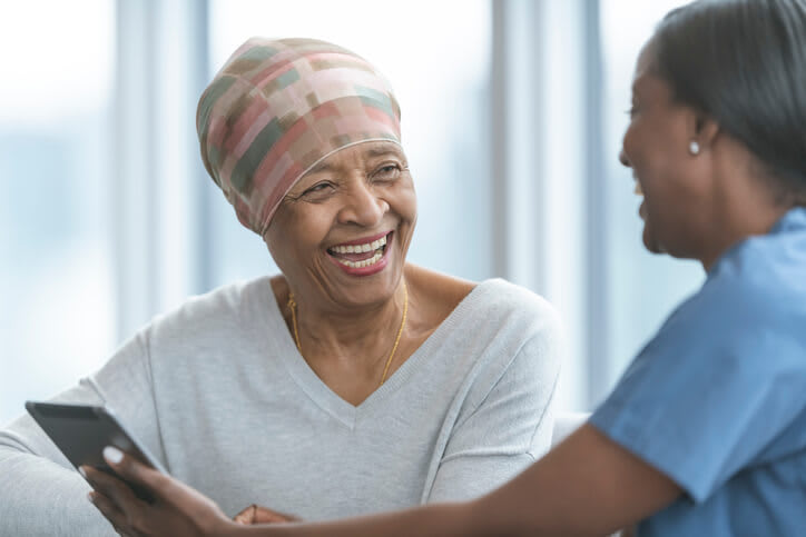 Woman in a head scarf laughs with her nurse