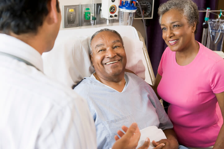 Couple smiles as they speak with doctor in hospital room