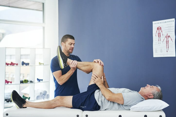 Physical therapist works with patient after knee replacement