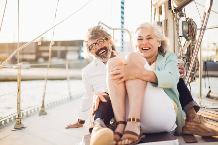 Smiling couple on a sailboat on a sunny day