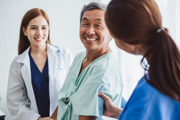 A man in hospital gown smiles as he talks with his nurses