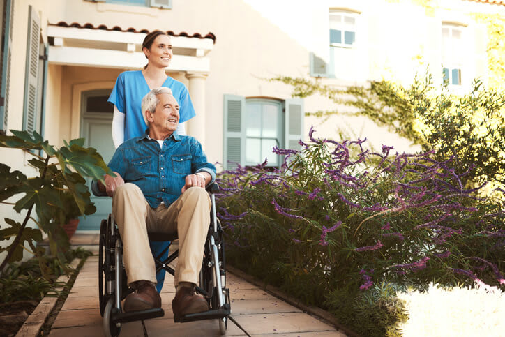 Long-term care nurse with her patient in a wheelchair outside