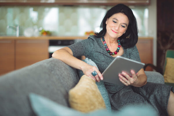 Woman sits on the couch using a tablet computer