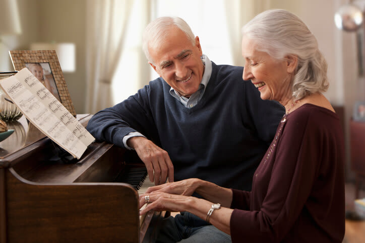 Couple sits at piano while wife plays