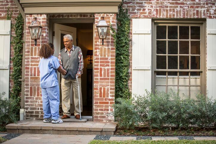A nurse meets a man using a cane at his front door