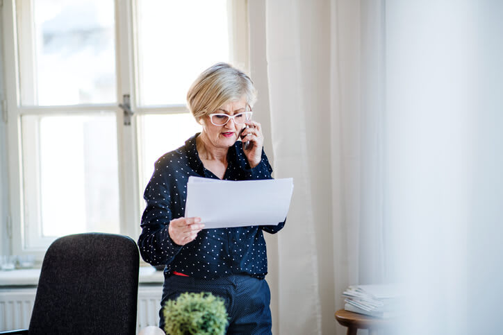 Woman on phone with paperwork