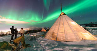 Traditional Sami tents (lappish yurts) in Norway offering tourists a comfortable place to watch the polar lights from after having a drink at an ice bar.