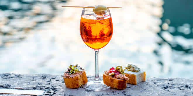 Spritz Aperol drink with traditional cicchetti snacks, some of the best foods to eat in Venice.