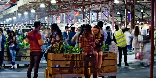 Shoppers enjoying a summer night at Queen Victoria Market, one of the best food markets in Melbourne.