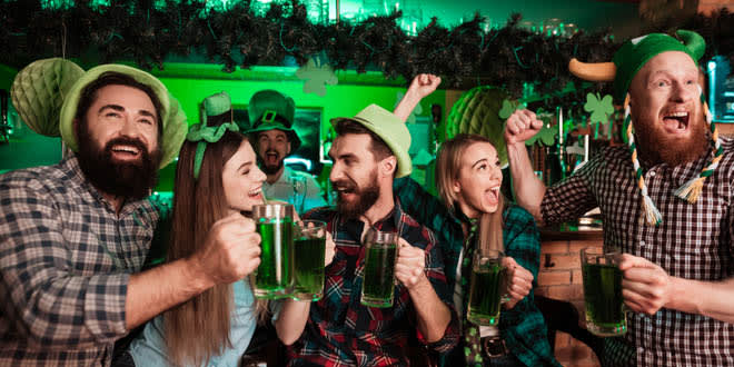 Young people celebrating St. Patrick's Day at a bar with green drinks and accessories.