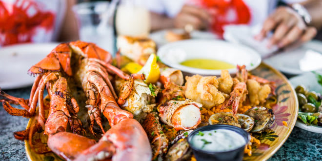 Lobsters and seafood on a plate with tartar sauce in one of the best seafood restaurants in Florida.