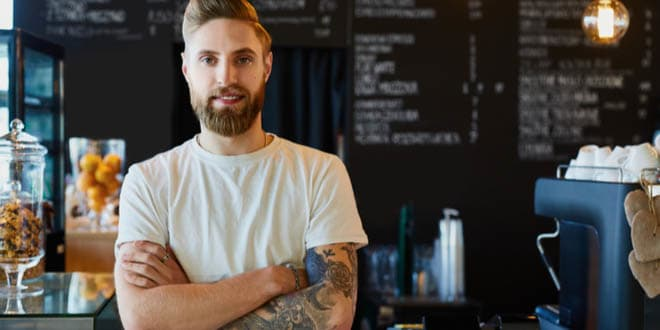 Male barista standing at a trendy coffee shop that serves some of the best coffee in LA.