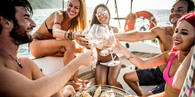 Group of young friends sailing for exotic cuisines and eating on deck