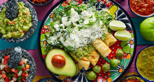 Buy international foods. Mexican green enchiladas with guacamole and sauces on colorful table.