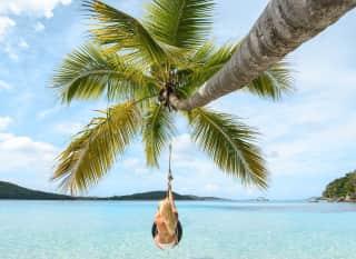 Fiji.woman swinging on palm tree