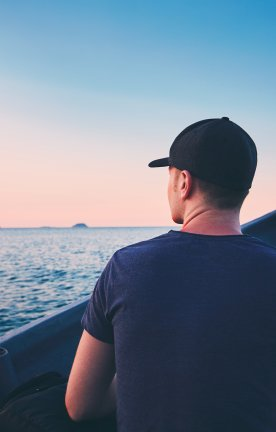 MY.Islands.with.man Man on boat with hat at sunset.