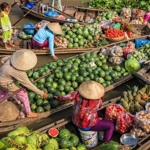 VN.Can_Tho_Floating_Markets Der Blick auf die mit Gemüse und Obst beladene Holzbote auf dem Fluss.