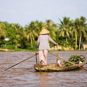 VN.Mekong-Delta_Bewohnerin Der Blick von Hinten auf eine Frau mit Reishut im Boot.