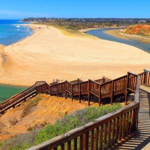 AU.Adelaide_Port_Noarlunga_Beach Der Blick über eine Holztreppe hinunter zu einer Lagune.