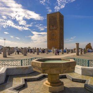 """MA.Rabat.Hassan_Turm Im Vordergrund ein verzierter Brunnen, im Hintergrund Blick auf das unvollendete Minarett des historischen """"Hassan Turm"""" in Rabat, Marokko"""