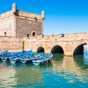 MA.Essaouira.Fischerboote Fort von Essaouira in Marokko an einem sonnigen Tag mit blauen Booten auf dem davor liegenden Wasser