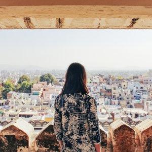 IN.Udaipur Frau steht über den Dächern einer Stadt in Indonesien