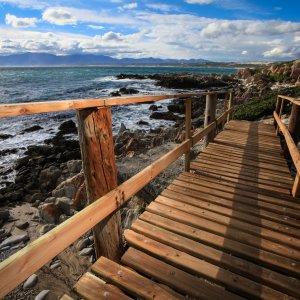 ZA.Hermanus.Promenade Hölzerne Brücke vor der Küste von Hermanus in Südafrika