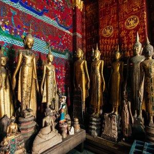 Laos.Wat_Xieng_Thong_Statuen goldene Buddhastatuen vor antiken, bunten Wandmalereien