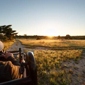 ZA.POI.Sabi Sand Game Reserve Safari Eine Person in einem Safari-Auto bei Sonnenuntergang