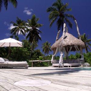 """SC.North_Island_Bungalow Kleine Lodge und Liegestühle unter Palmen im Ferienclub """"North Island Lodge"""" auf der Insel North Island, Seychellen"""
