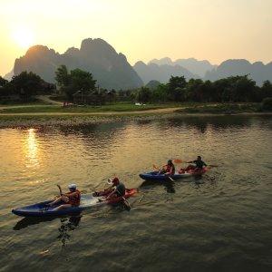 LA.Vang_Vieng_Kajak_Trips Der Blick auf den Nam Song River mit Menschen in Kajaks umgeben von der mit Feldern und Kalksteinformationen geprägten Landschaft in Vang Vieng, Laos bei Dämmerung.