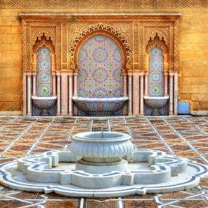 MA.Rabat.Brunnen Pompös verzierter Brunnen mit marmorierten Becken an den Wänden im Hintergrund, nahe des Mausoleum von Mohammed V in Rabat, Marokko