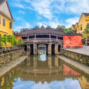 VN.Hoi_An_Japanische_Brücke Der Blick auf eine japanische Brücke über einen Fluss umgeben von gelben Häusern.