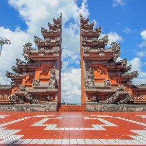 Bali.Denpasar.Eingangstor Zwei orangene, verzierte Türme bilden ein Tor