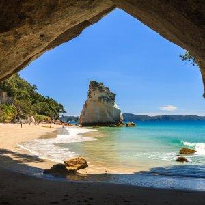 NZ.Coromandel_Halbinsel_Cathedral_Cove Der Blick aus einer Höhle über die Bucht mit Felsformation.