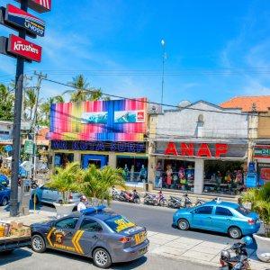 Bali.Kuta.Stadt Autos fahren auf einer Straße mit Geschäften
