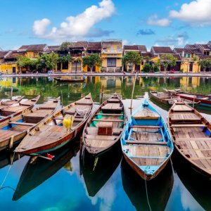 VN.Hoi_An_River Der Blick auf den Fluss mit bunten Holzbooten und gelben Häusern im Hintergrund.