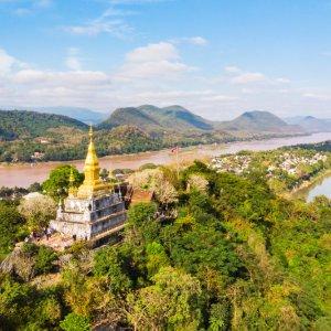 LA.Luang_Prabang_Phu_Si Der Blick auf den Hügel Phu Si mit goldener Paode und die umliegende Landschaft inmitten der Stadt Luang Prabang, Laos.