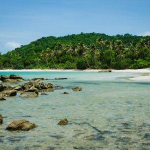 VN.Phu_Quoc_Strände Der Blick auf einen unbelebten Strand mit zahlreichen Palmen, weißem Sand und klarem türkisblauem Wasser.