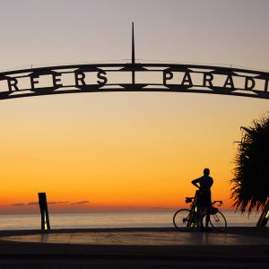 AU.Gold_Coast_Surfers_Paradise Der Blick bei Sonnenuntergang auf einen Bogen der die Buchstaben Surfer Paradise zeichnet.